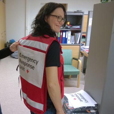 SPR:n henkilöstöassistentti Pia Pasma auttaa Jordaniaan avustustyöntekijäksi lähtevää Kati Marttista sovittamaan työliiviä.