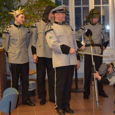 Sotilaspuvuissa olevat miehet esittävät Tiernapoikia.