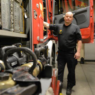 Mies seisoo paloauton ovella. Etualalla pelastusvälineitä.