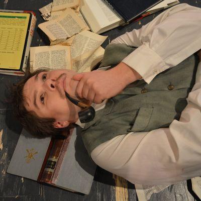 mies makaa lattialla kirjapino ympärillä
