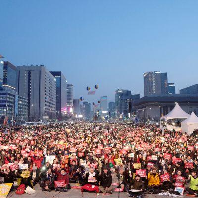 Ihmisiä istuu kadulla Soulissa.