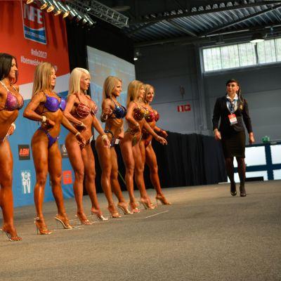 Bikini fitness -kilpailijoita poseeraa lavalla.