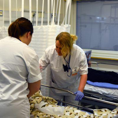 Sairaanhoitajat hoitamassa vanhusta Vaasan kaupunginsairaalan vuodeosastolla numero viisi.