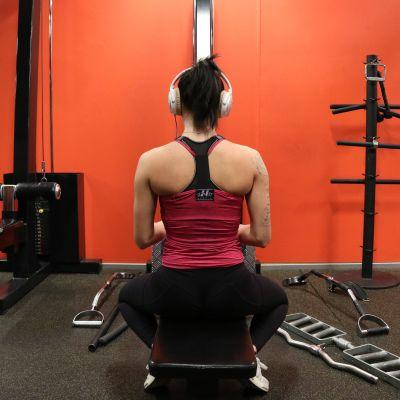 Nainen istuu penkillä kuulokkeet korvilla