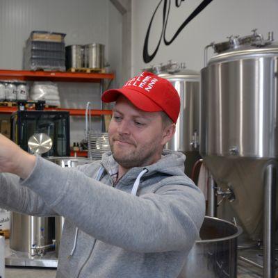Daniel Löf paketoi olutpulloja laatikkoon.