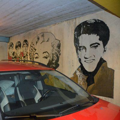 Parkkihallin seiniä komistavat niin Beatles, Elvis, Marilyn kuin vanhat autotkin.