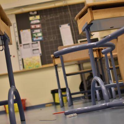 Kaadettu tuoli ja levinneet työvalineet koulun luokassa