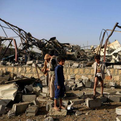 Barn samlar metallskrot vid en husruin efter en saudisk flygräd i Jemens huvudstad Sanaa den 20 januari 2019.