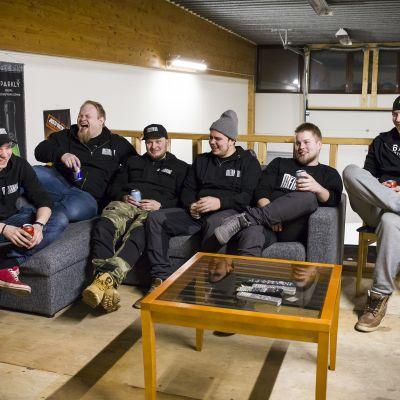 Miehiä istumassa sohvalla.