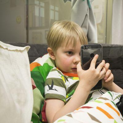 Jirka Jonninen pelaa matkapuhelimellaan Perheentuvalla Kuopiossa.