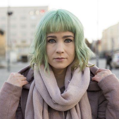 Henna tittar rakt in i kameran. Hon står på ett torg och håller i jackans huva som hon fällt ner. Hon har turkosa hår och stark kajal målad kring ögonen.