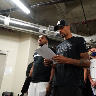 George Hill of the Milwaukee Bucks reads a statement to the media
