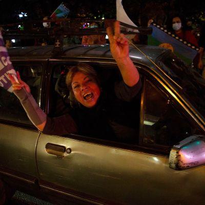 nainen heiluttaa lippuja autosta