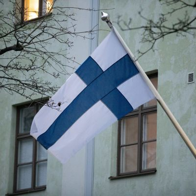 Suomen lippu liehuu vihreän kerrostalon edessä