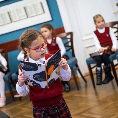 Virolainen koulutyttö tutkii kirjaa.