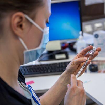 Terveydenhoitaja valmistelee rokoteannoksia rokotepulloista.