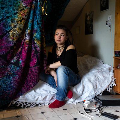 Emma Rask istuu patjalla lattialla ja katsoo ulos.