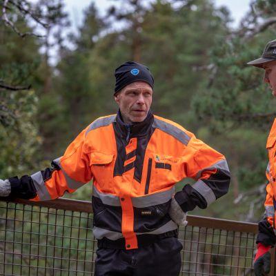 Metsähallituksen rakennusmestari Pasi Ikonen ja Repoveden kansallispuiston puistomestari Mikko Suosalmi seisovat Lapinsalmen sillankaiteen vieressä.