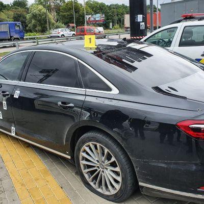 en svart bil står parkerad på en parkeringsplats. Bilen har flera skotthål.