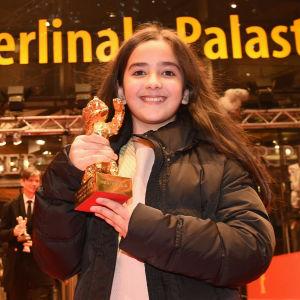 Hanna Saeidi med sin guldbjörn på röda mattan i Berlin.