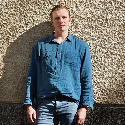 Kirjailija Pärttyli Rinne seisoo muurin edessä