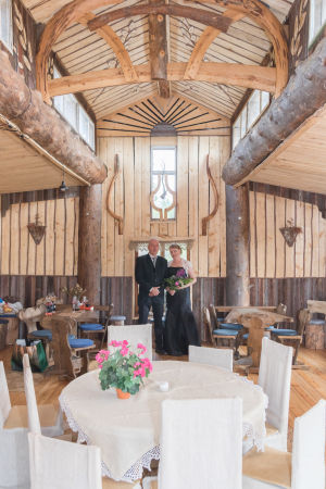 Hääpari puusta tehdyssä rakennuksessa, oksilla koristeltuja seiniä, valkoisin liinoin peitettyjä pöytiä.