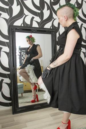 En kvinna med grönt hår står framför en helkroppsspegel och speglar sig.