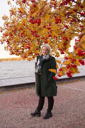 En blond kvinna med glasögon. Står framför en rönn med röda bär. I bakgrunden syns havet.