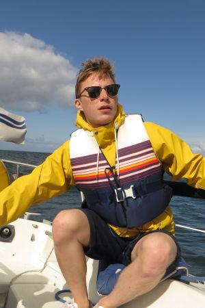 Lucas Dahlström seglar iklädd gul regnjacka och flytväst.
