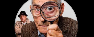 En gammal man i närbild tittar in i kameran med ett förstoringsglas. I bakgrunden syns en annan man.