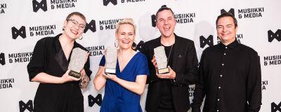 Kuvassa neljä ihmistä kolmen palkinnon kanssa Industry Awardsissa.