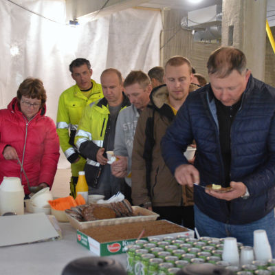 Män tar åt sig mat vid en taklagsfest.