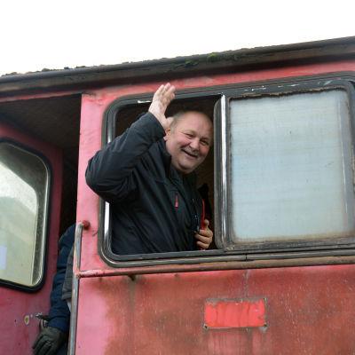 Jari Häkkinen står i ett lok och vinkar genom fönstret.