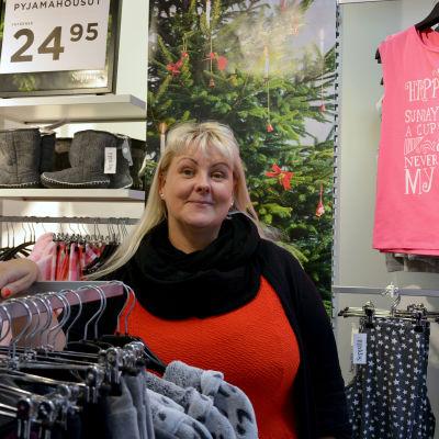 Marina Strömberg står vid en klädställning.