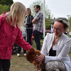 Pia Smeds med barn som klappar en höna.