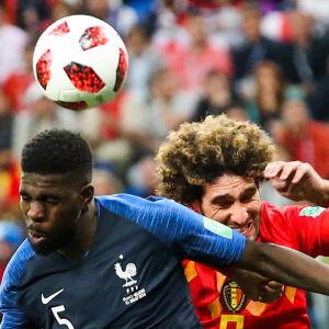 Frankrikes Samuel Umtiti vinner nickduellen mot belgiska mittfältaren Marouane Fellaini och för upp Frankrike i ledningen i VM-semifinalen.
