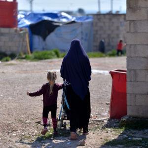 Nainen ja lapsi kävelevät leirillä selin kameraan.
