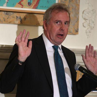 Kim Darroch, en äldre man i kostym, håller upp händerna i luften under en presskonferens.