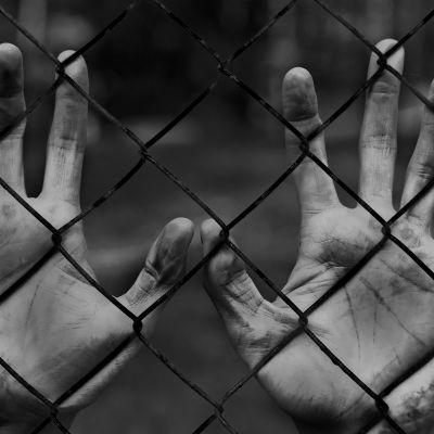 En person fängslad. Händer på fängsel.