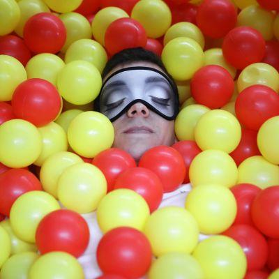 Mies makaa pallomeressä unimaski kasvoillaan.