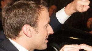 Frankrikes president Emmanuel Macron i profil. Han ler och höjer näven som i hälsning.