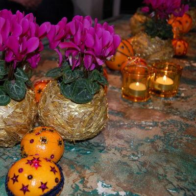 Ett bord som dekorerats med ceriserosa minicyklamenblommor, värmeljus i gula glaslyktor och mandariner och palesiner som dekorerats med paljetter och sidenband i olika mönster.