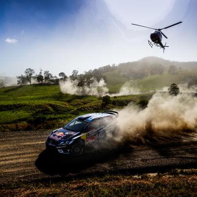 Latvalas Volkswagen kurvar framför en helikopter.