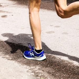 Asfaltilla juostaan juoksulenkkiä. Kuvassa jalat ja ihmisen varjo.