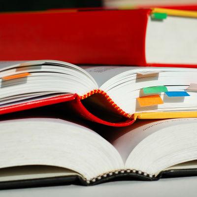Två öppna böcker ligger på varandra.