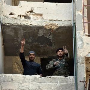 Syriska soldater gör segertecken i fönstret till ett rasat hus i Aleppo.