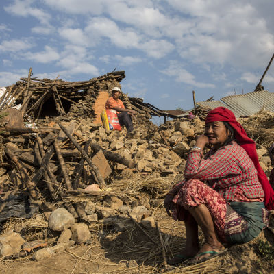 Nepalesisk familj vid ruinerna av sitt hem efter jordbävning