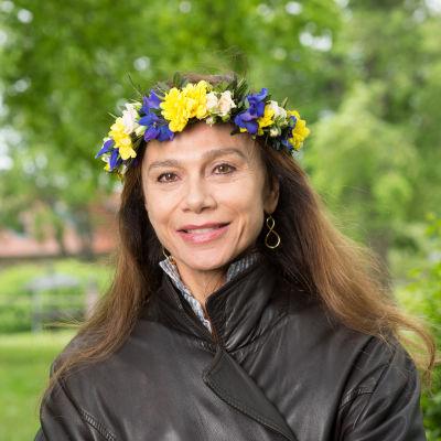 Skådespelare Lena Olin med blomsterkrans i håret.