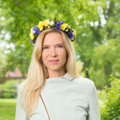 Författare Liza Marklund med blomsterkrans i håret.