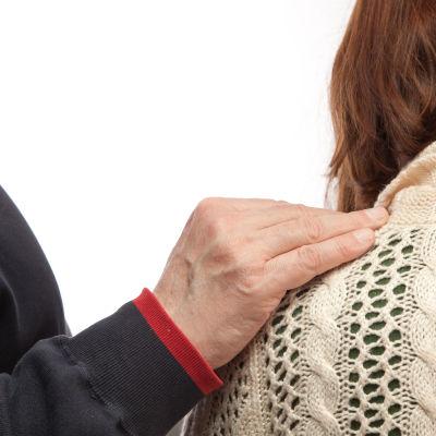 Deltagande hand på axel